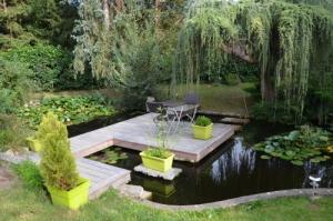 Terrasse bois sur un plan d'eau intégré dans un jardin d'une maison particulière